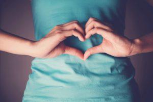 Ayurvedamagazin-Darm_Frau-zeigt-auf-Darm-mit-Herz