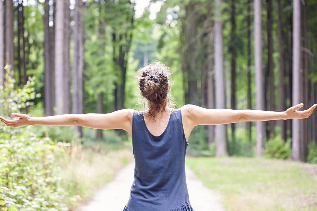 Ayurvedamagazin-Sehnsuchtsort-Natur_Frau-im-Wald-in-Freude